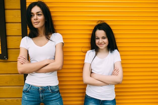 Twee brunette meisjes staan tegen oranje muur