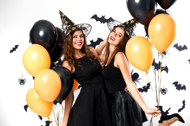 Twee brunette vrouwen in zwarte jurken en heksenhoeden houden zwarte en oranje ballonnen op de achtergrond van de muur met vleermuizen. halloween feest .