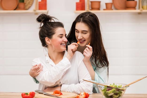 Twee brunettes voeden elkaar met plakjes rode peper