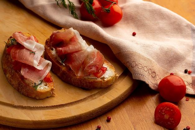 Twee bruschetta's met tomaat en jamon op een houten bord naast een servet en kerstomaatjes