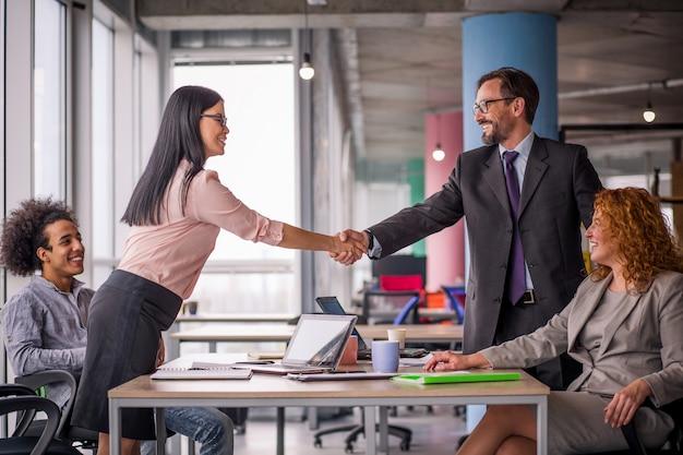 Twee business teams met succes onderhandelen, handen schudden.