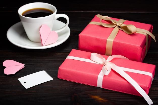 Twee cadeaus verpakt in cadeaupapier, een papieren label en een kopje koffie op een donkere tafel.