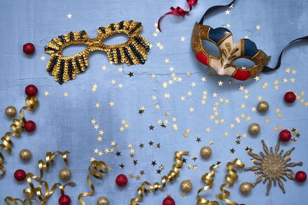 Twee carnaval-maskers, confettiensterren en partijwimpels op blauwe achtergrond.