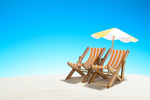 Twee chaise longue onder een parasol op het zandstrand