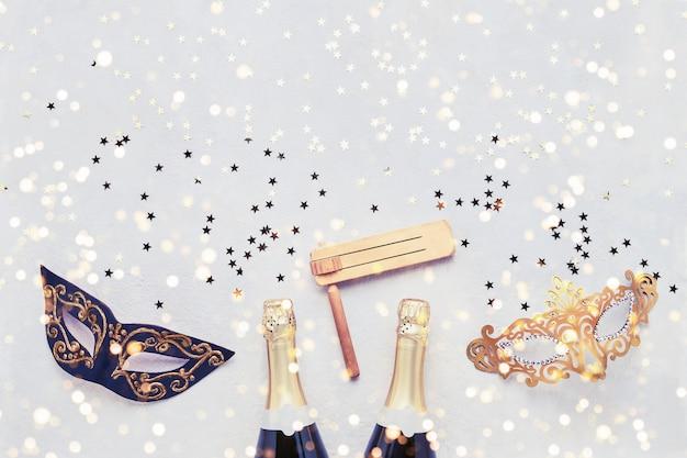 Twee champagneflessen, carnaval masker en gragger op lichte achtergrond. plat leggen van purim carnaval viering concept.