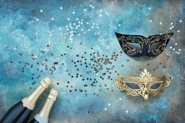 Twee champagneflessen, carnaval maskers en confetti sterren op kleurrijke achtergrond.