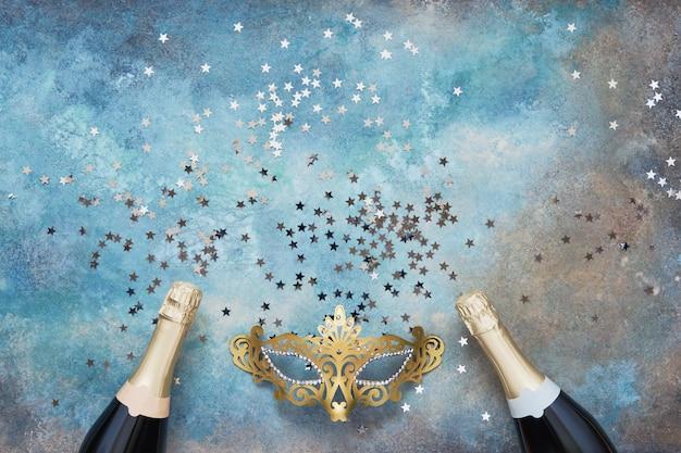 Twee champagneflessen, gouden carnaval masker en confetti sterren op blauwe achtergrond.