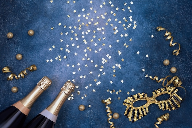 Twee champagneflessen met carnaval masker confetti sterren en partij slingers op blauwe achtergrond