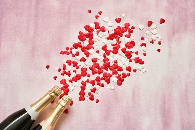 Twee champagneflessen met rode en witte harten op roze achtergrond.