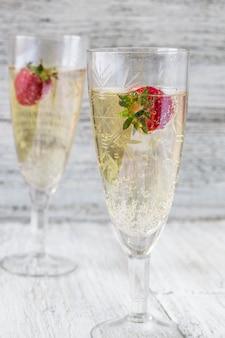 Twee champagneglazen en aardbeien op witte achtergrond