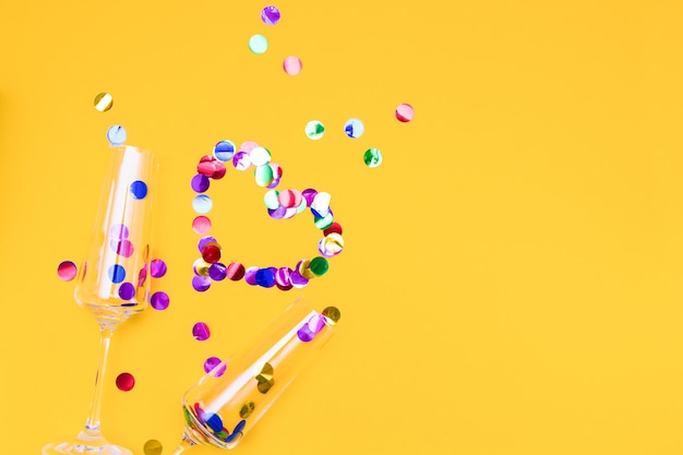 Twee champagneglazen en confetti op gele achtergrond