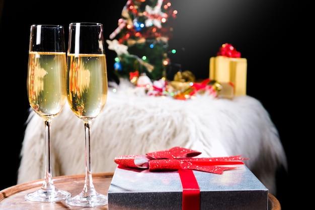 Twee champagneglazen en geschenkdozen met kerstboom op achtergrond