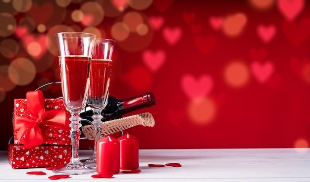 Twee champagneglazen, geschenkdozen en kaarsen op mooie bokeh achtergrond met kopie ruimte