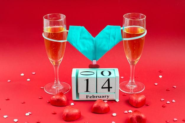 Twee champagneglazen, houten kalender, suikergoed en medisch maskervalentijnskaart op rood.