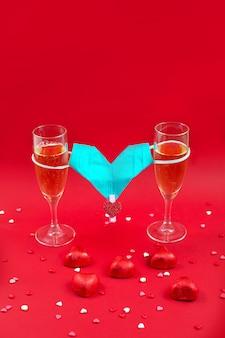 Twee champagneglazen, suikergoed en medische maskervalentijnskaart op rood.