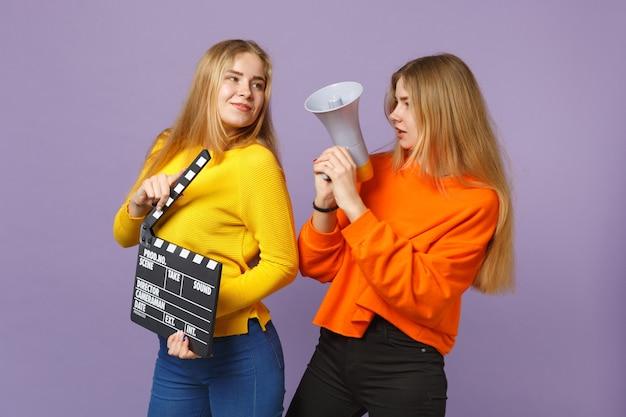 Twee charmante jonge blonde tweelingzusters meisjes houden klassieke zwarte film filmklapper, schreeuwen op megafoon geïsoleerd op violet blauwe muur. mensen familie levensstijl concept. .
