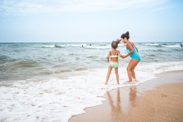 Twee charmante kleine meisjes in zwemkleding dansen op een zandstrand in de buurt van de zee tegen de blauwe lucht op een warme zomerdag