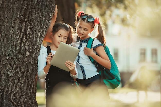 Twee charmante schoolgaande meisjes staan bij de boom bij de school en spelen op de tablet.