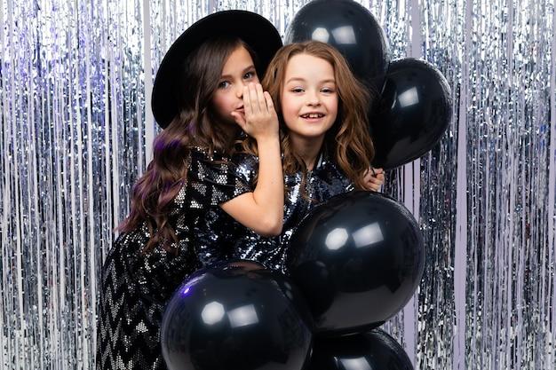 Twee charmante stijlvolle jonge zusters in vakantie jurken met zwarte ballonnen op een feestje op een glanzende muur