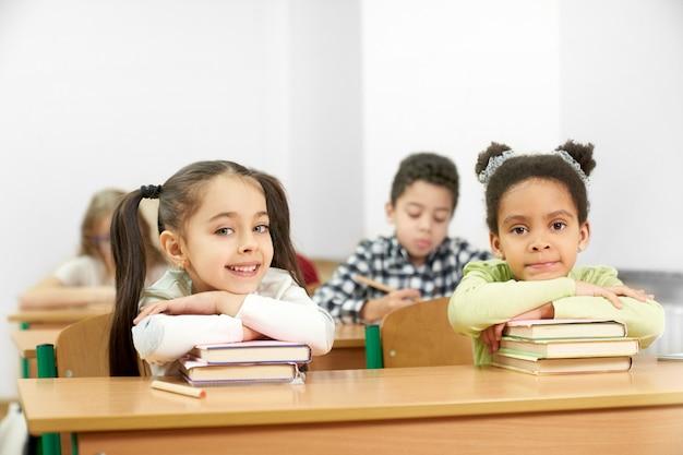 Twee charmante studenten zitten aan tafel in school en poseren