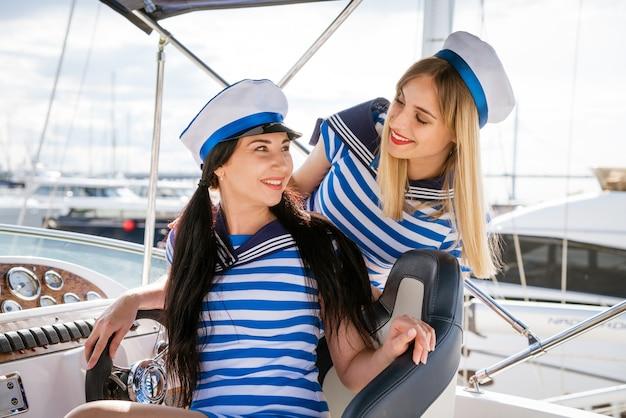Twee charmante vrouwen met lang haar in jurken in nautische stijl zitten op het jacht