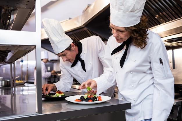 Twee chef-koks die maaltijd op teller versieren