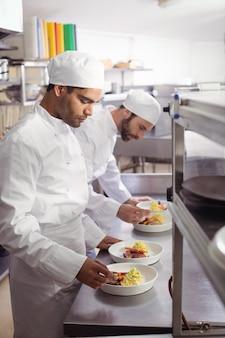 Twee chef-koks die voedsel in commerciële keuken versieren
