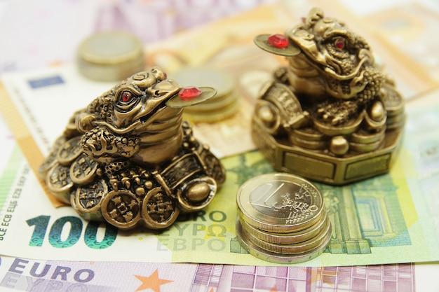Twee chinese feng shui-kikkers die op eurobankbiljetten zitten. symbool van overvloed en geluk.