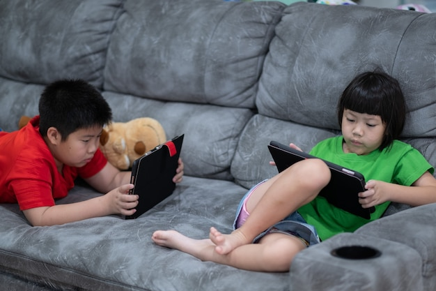 Twee chinese kinderen verslaafde tablet, aziatisch kind kijken samen naar de telefoon op hun bed, kind met smartphone