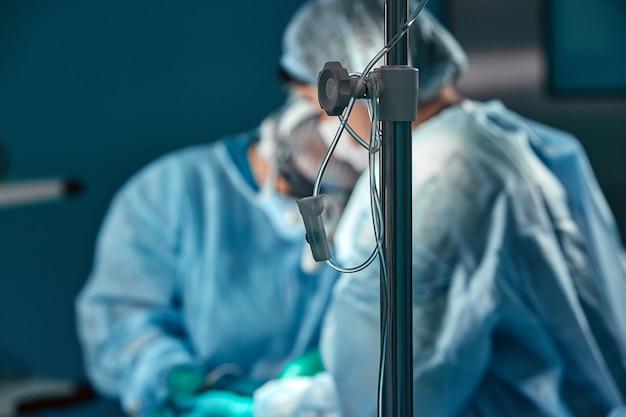 Twee chirurgen in beschermende uniform tijdens de operatie, op de achtergrond van de chirurgische kamer. oogpunt geschoten