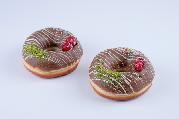 Twee chocolade donuts versierd met hagelslag en bessen op wit.