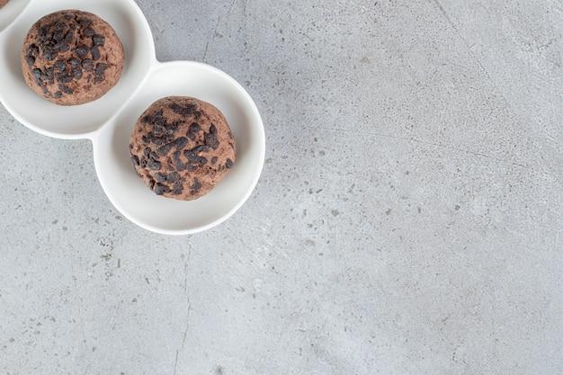 Twee chocoladekoekjes op een schaal op een marmeren oppervlak