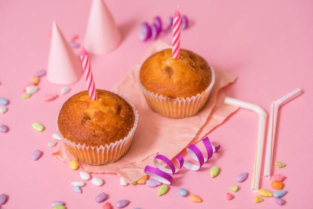 Twee chocolademuffins, een verjaardagskaars. feest voor meisjes. caps en klatergoud en veelkleurige snoepjes op een roze achtergrond.