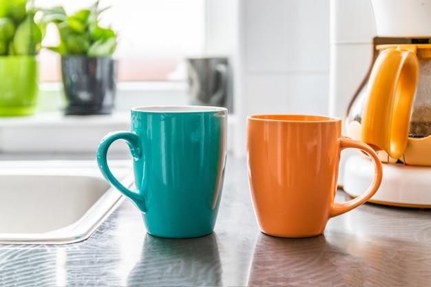 Twee cirkels met een warme drank staan op de tafel. op de achtergrond staat een koffiezetapparaat en een pot met groene planten.