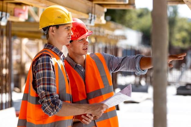 Twee civiel ingenieurs gekleed in oranje werkvesten en helmen bespreken het bouwproces op de bouwplaats bij de houten constructies en stalen frames.