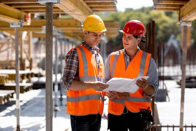 Twee civiel ingenieurs gekleed in oranje werkvesten en helmen onderzoeken bouwdocumentatie op de bouwplaats bij de houten bouwconstructies.