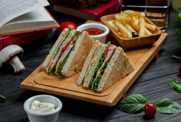 Twee clubsandwiches met cheddar en spek geserveerd met sauzen en friet