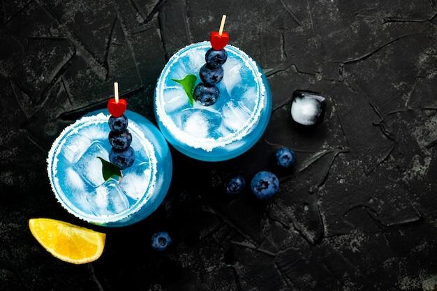 Twee cocktails met ijs, blue curacao en bosbessen