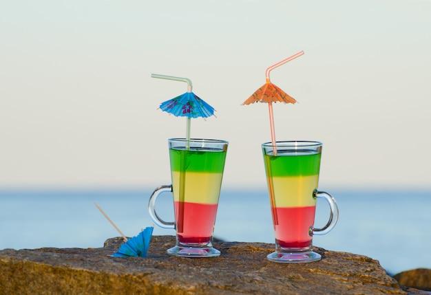 Twee cocktails met rietjes op een rots in de buurt van de zee