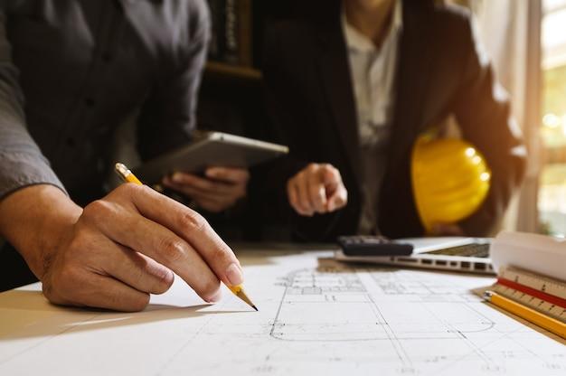 Twee collega's bespreken gegevens werken en tablet, laptop met op architecturaal project op bouwplaats bij balie in kantoor