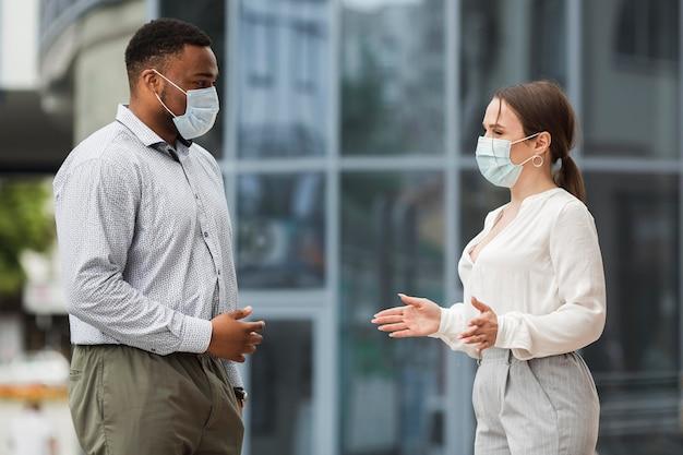 Twee collega's chatten buiten tijdens pandemie met maskers