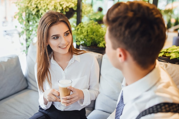 Twee collega's communiceren tijdens een pauze in een slimme ruimte. gekleed in witte overhemden