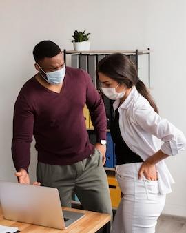 Twee collega's die op kantoor werken tijdens een pandemie met maskers aan