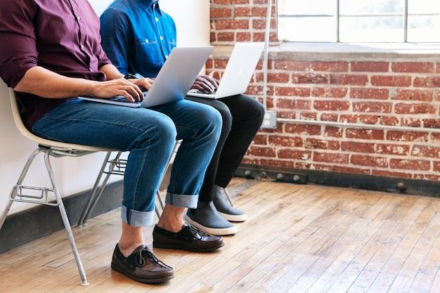 Twee collega's die samenwerken op hun laptop
