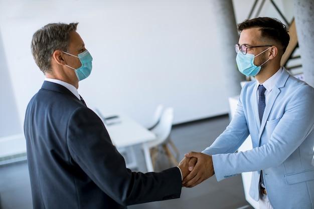 Twee collega's handdruk tijdens een ontmoeting op kantoor
