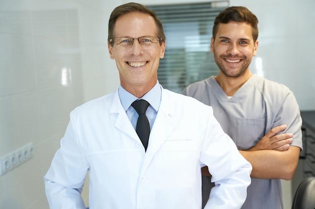 Twee collega's in de tandheelkundige kliniek poseren voor de camera