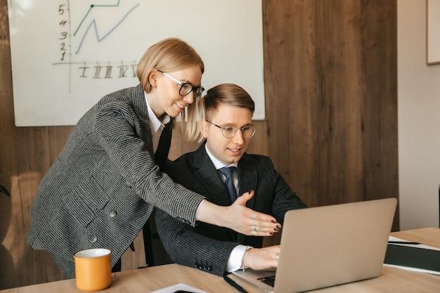 Twee collega's kijken naar documenten en werken op een laptop, secretaris of vrouw manager leest een document, glimlachende zakenvrouw.