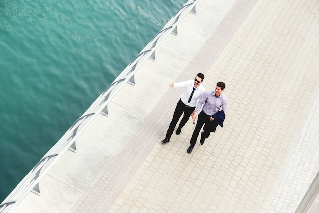 Twee collega's lopen langs de rivierpromenade. bespreking van belangrijke zakelijke onderwerpen op weg naar kantoor.