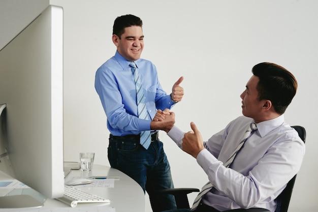 Twee collega's met duimen omhoog handen schudden als teken van goed werk