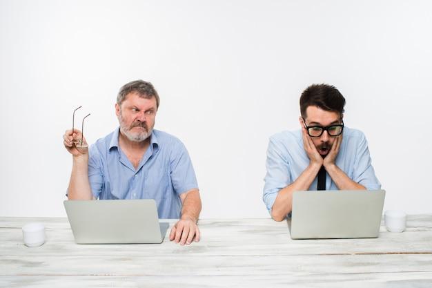 Twee collega's samen te werken op kantoor op wit